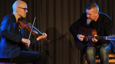 Esko Järvelä & Roger Tallroth soittavat yhdessä. Eskolla on viulu ja Rogerilla kitara. Molemmat istuvat ja tuijottavat toisiaan samalla kun he soittavat.