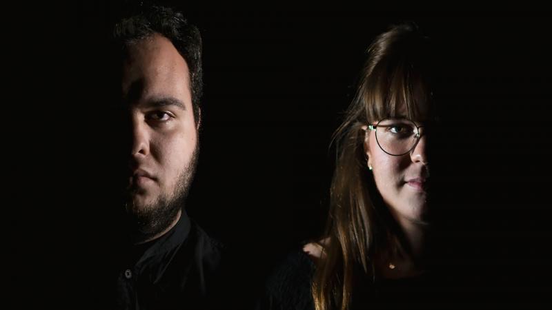Claudia Reyes Segovia ja Pau Fernández Benlloch seisovat tummassa huoneessa. Vain puolet molempien kasvoista näkyy kuvassa kaiken mustan keskellä.