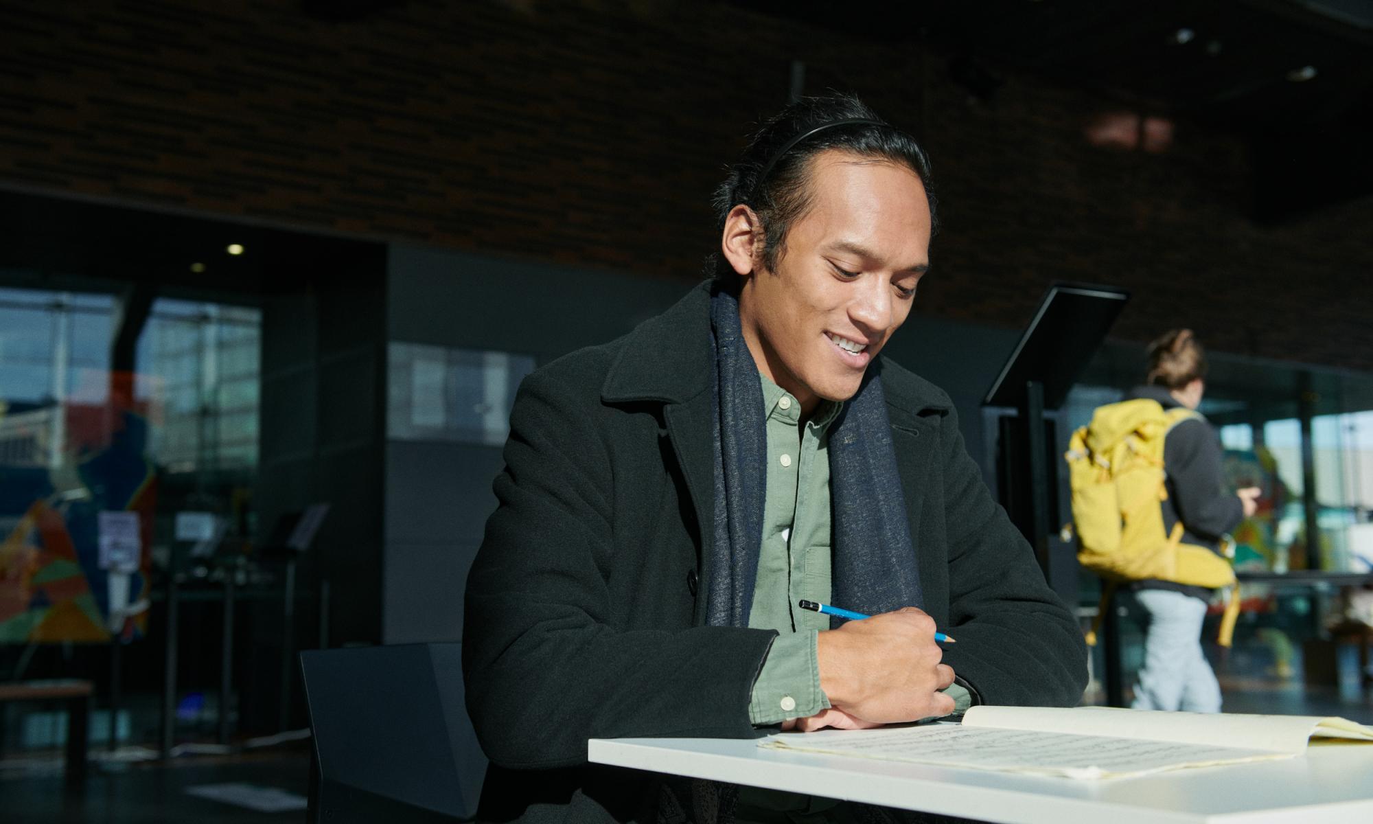 mies kirjoittaa pöydän ääressä