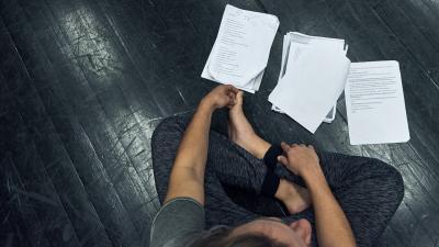 Opiskelija istuu lattialla risti-istunnassa. Opiskelijan edessä lattialla on kolme pinoa papereita, joissa on käsikirjoituksia.