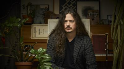 The man is sitting in a room where there are many plants. He looks straight ahead at the camera. The man has quite long hair.