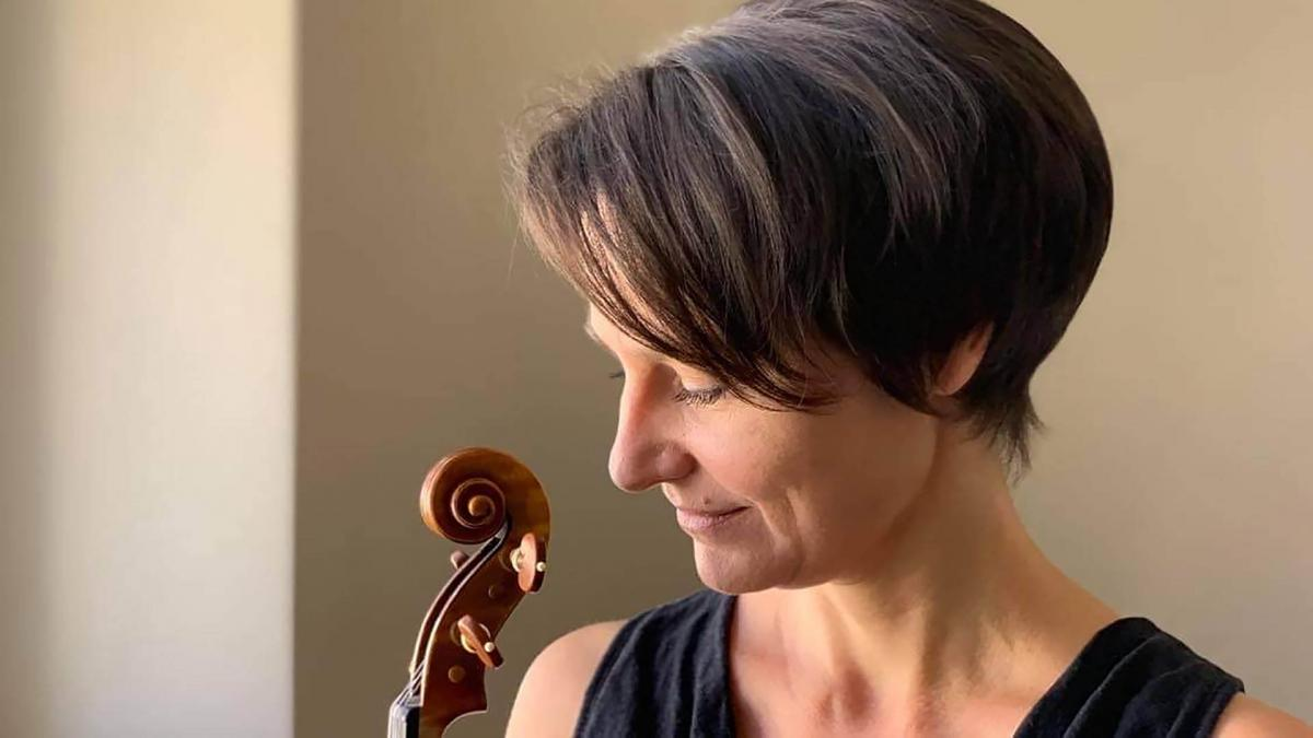 Réka is posting in front of widow with her violin. She is looking down and smiles.