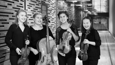 Aino Yamaguchi, Julie Svacinova ja Siiri Nieminen hymyilevät kameralle mustavalkoisessa kuvassa. Kuvassa heillä on instrumentit käsissään. Kuva on otettu Musiikkitalossa konserttisalin takaovella.