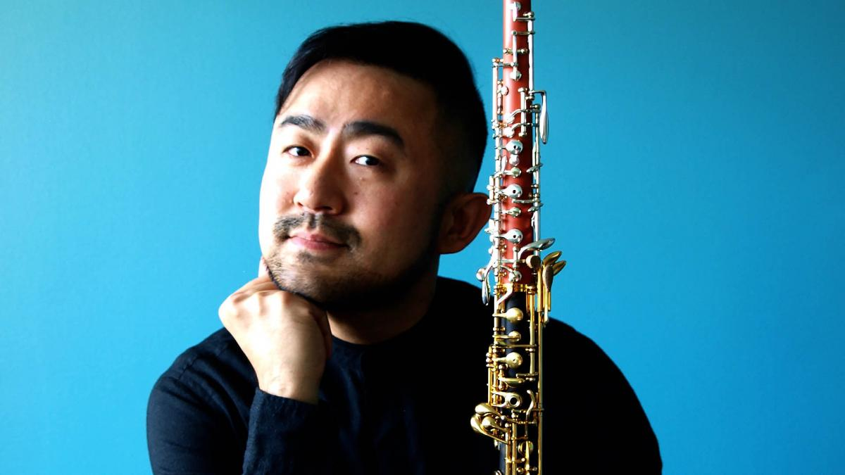 Takuya Takashima leans on his hand and holds oboe with his another hand and smiles gently. The background of the picture is bright blue.