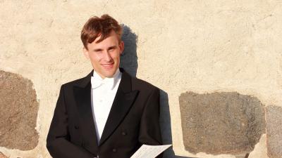 Henrik Järvi hymyilee kameralle keltaista seinää vasten. Kuva on otettu ulkona auringonpaisteessa. Henrikillä on puku päällä ja hän selaa nuotteja.