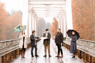 Echo Percussions -yhtye seisoo sillalla valokuvassa. Ulkona on sateinen keli, mutta kaikki ovat iloisia.