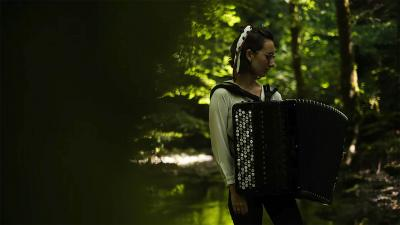 Woman is standing in the forest with accordion.