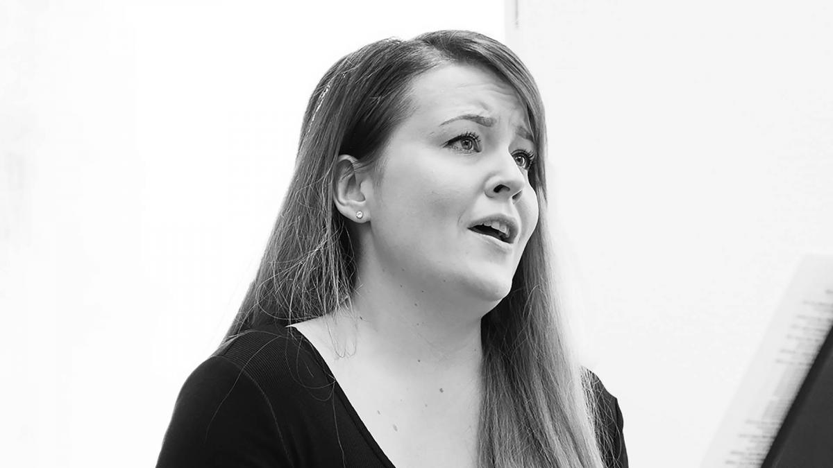Woman is singing in a black and white portait.