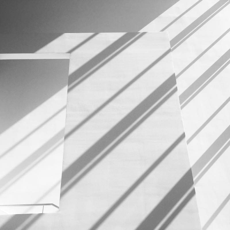 Valoa ja varjoa valkoisella seinäpinnalla.