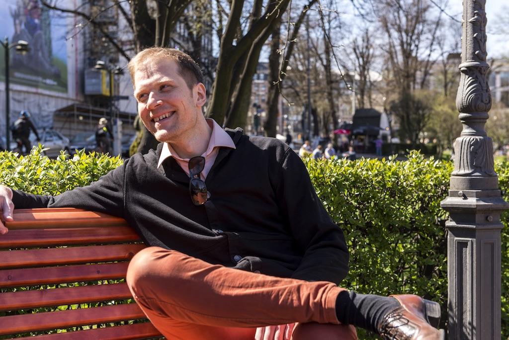 Ville Komppa istuu puistonpenkillä hymyillen.