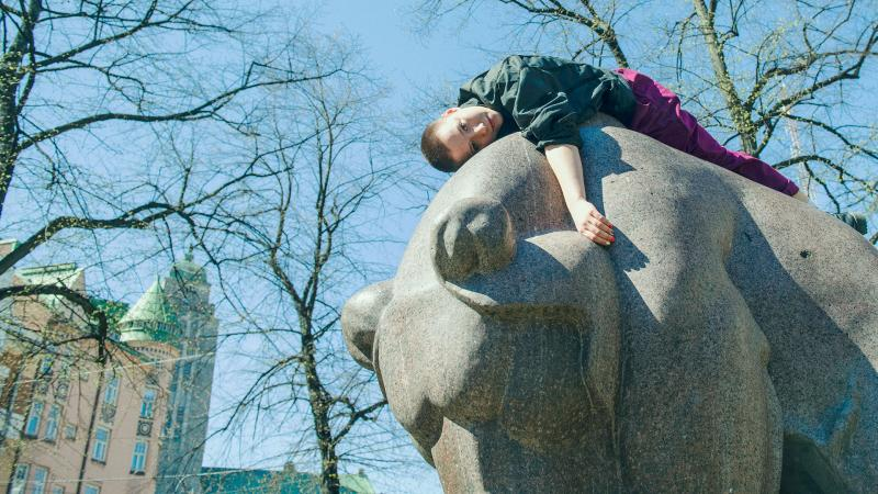 Woman is lying on top of the bear statue at Karhupuisto, Helsinki.