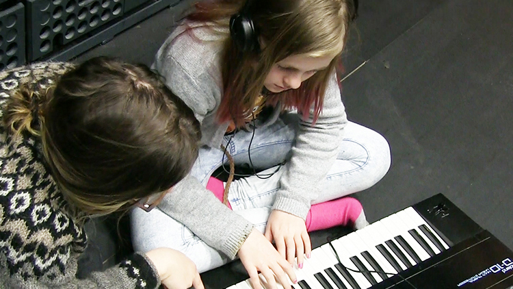 Opiskelija ja lapsi työskentelevät keyboardin ääressä