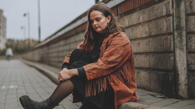 Emmi Hakala istuu katukiveyksellä nojaten jalkoihinsa käsillään. Hän katsoo alaspäin.