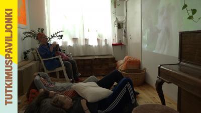 Olohuoneessa ihmisiä katsomassa videota.