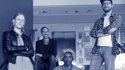 Neljä yhtyeen jäsentä poseeraa portaikossa sinisävyisessä kuvassa.