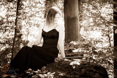 Liisa Tamminen istuu metsässä kiven päällä viulu vierellään.