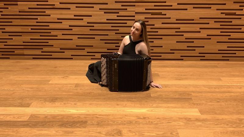 Manca istuu Musiikkitalon konserttisalin lattialla haitarinsa kanssa ja hymyilee.