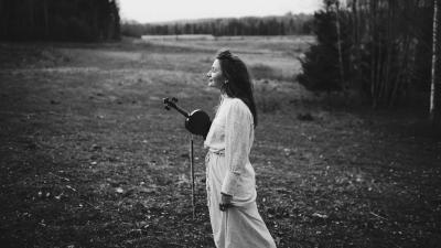 Kärt Tambet stands in the field eyes closed with a little smile on her face.