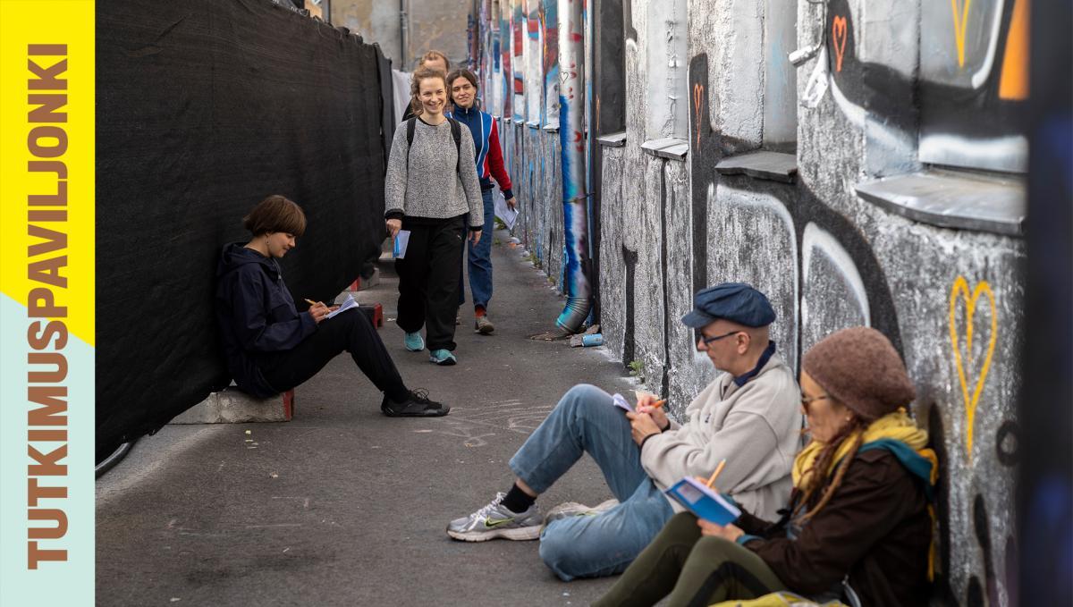 Ihmiset istuvat maassa ja piirtävät.