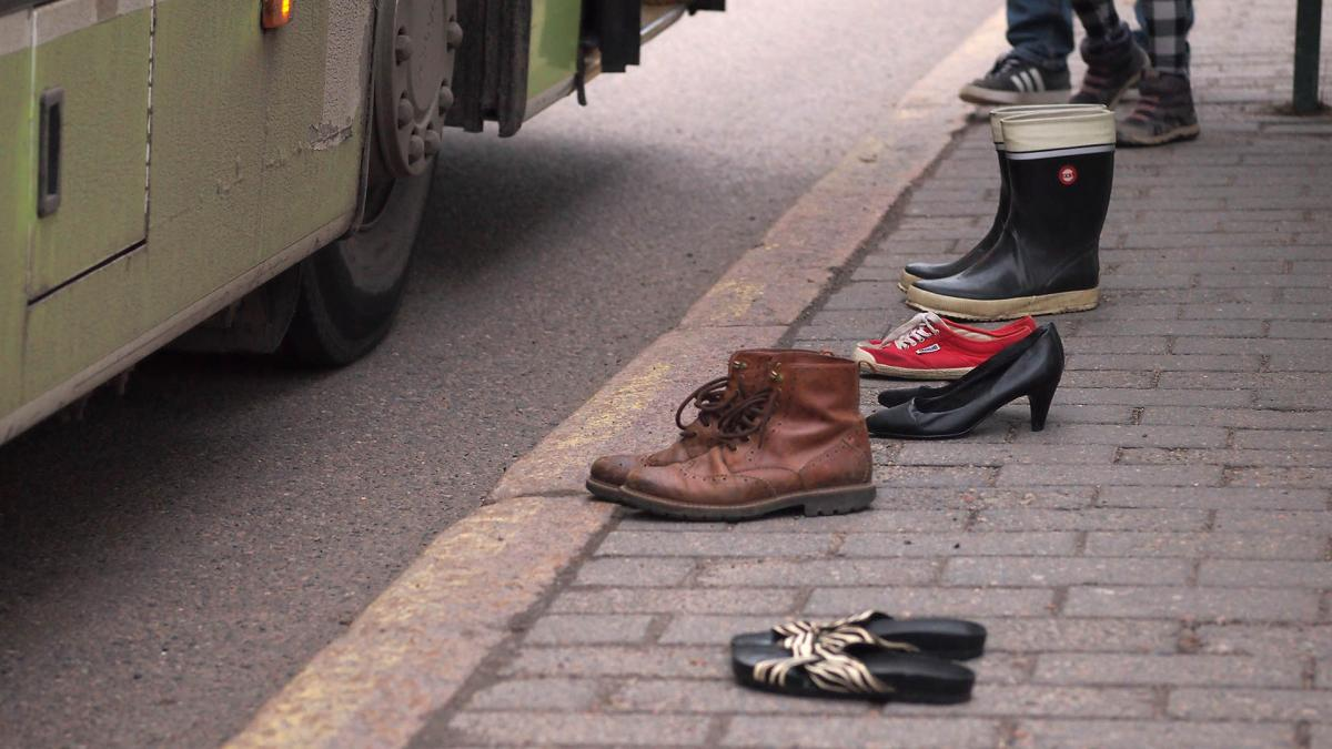 Picture of a shoes that are standing alone at a bus stop