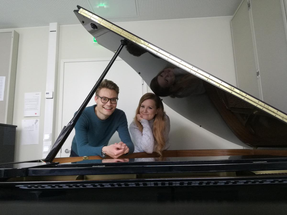 Young man and a young woman behind a piano