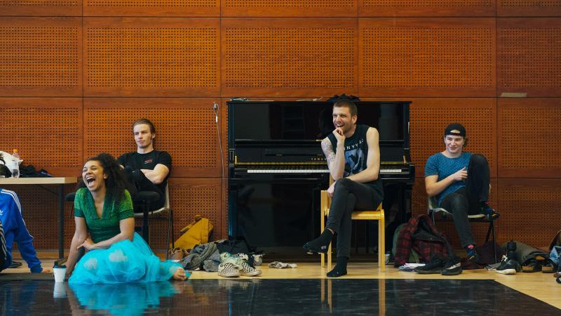 Pieni joukko opiskelijoita istuu harjoitussalissa, osa tuoleissa, osa lattialla. Taustalla musta piano.
