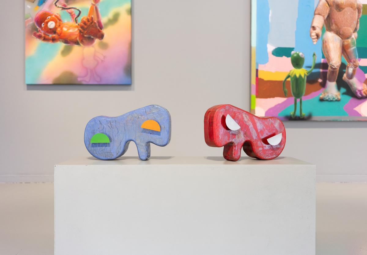 Kaksi värikästä, alkuolentoa muistuttavaa veistosta jalustalla. Taustalla osia värikkäistä maalauksista.