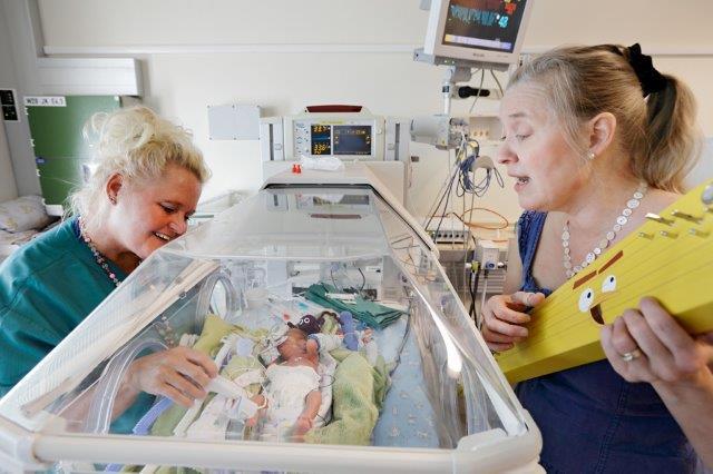 Sairaalamuusikko soittaa kannelta keskoselle, hoitaja katselee toiselta puolelta keskoskaappia.