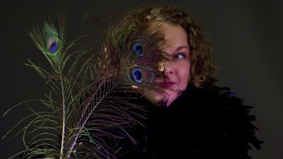 Nainen riikinkukon höyhen kasvojen edessä