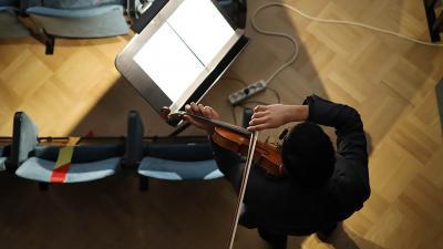 Viulisti soittaa viulua konserttisalin tyhjässä katsomossa.