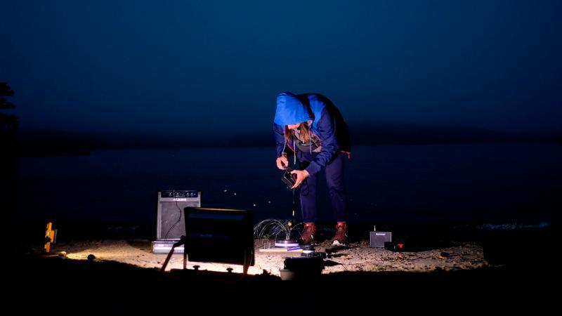 Ulkona pimeässä Dmitri Zherbin tuulipuvussa huppu päässä, hieman kumarassa asennossa, ympärillään ja kädessään audiolaitteita. Maata valaisee yksi valonlähde.