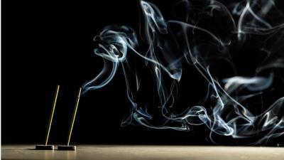 Kaksi suitsuketta palaa pöytäpinnalla ja levittää vaaleana erottuvaa savua ympäröivään tilaan tummasävyisessä kuvassa.