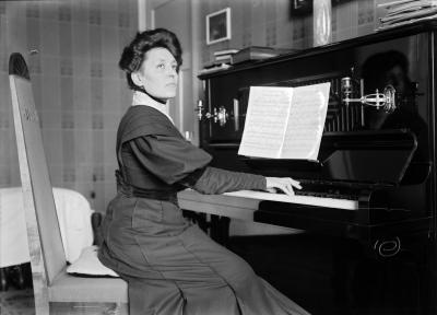 1800-luvulta oleva kuva, jossa nainen soittaa pianoa ja katsoo kameraan