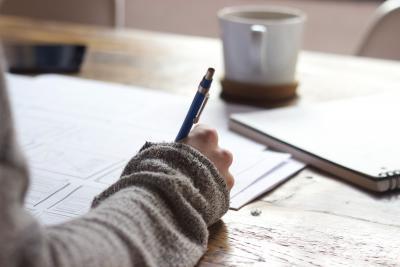 Henkilö kirjoittaa pöydän äärellä, hänestä näkyy vain kynää pitelevä käsi. Taustalla kuppi.