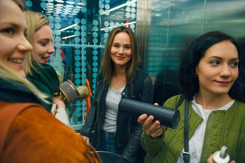 Opiskelijat hymyilevät hississä