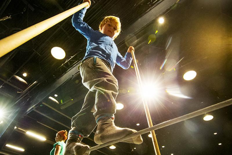Poikaoletettu lapsi kävelee narulla käsissään tasapainoa auttavat pitkät paalut. Kuva on otettu alhaalta, poika katsoo kameraan, taustalla näkyy naisoletettu ja mustan salin kirkkaat spotit.