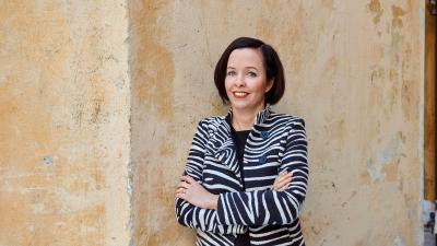 Dekaani Emilie Gardberg seisoo keltaisen rakennus taustallaan