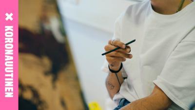 henkilö pitelee kynää kädessään