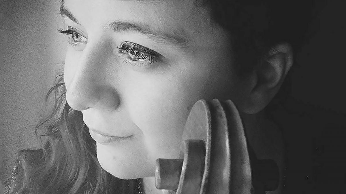 Sirja Nirosen kasvokuva ja poskeen nojaava sello