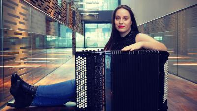 Manca is sitting on a Music centre hall with her accordion. She is smiling on the camera.