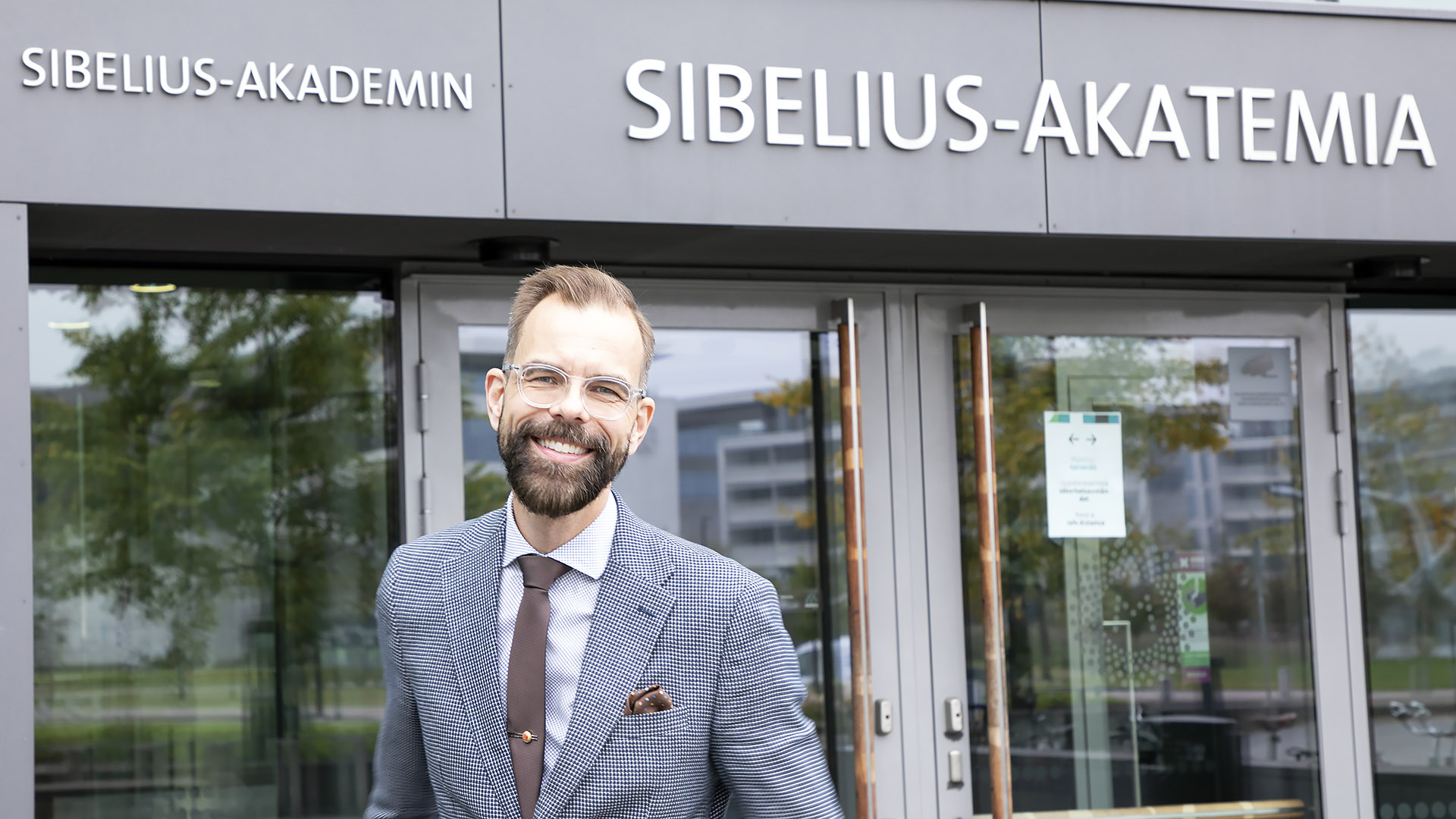 Markus Utrio stands outside of Sibelius Academy's main entrance at Helsinki Music Centre