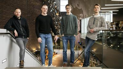 The Sibelius Jazz Quartet seisoo Musiikkitalon Mannerheimintien sisäänkäynnin viereisillä portailla ja hymyilee kameralle.