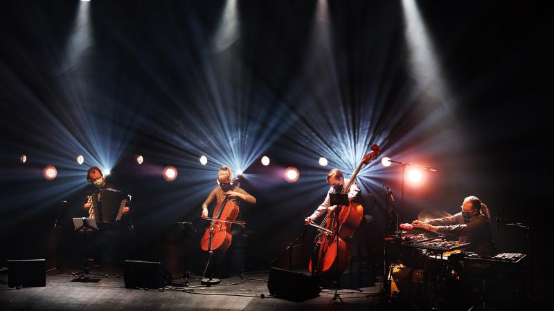 Drummer, two cellists and accordionist playing on a stage.