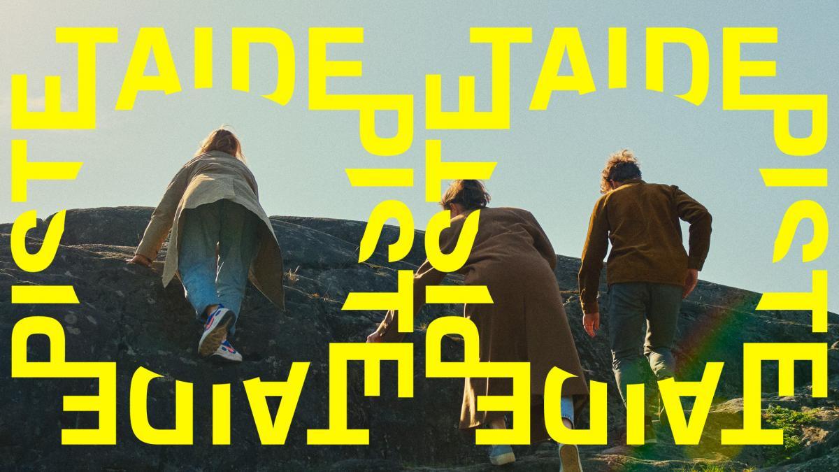 Kolme opiskelijaa kiipeävät kalliota pitkin.