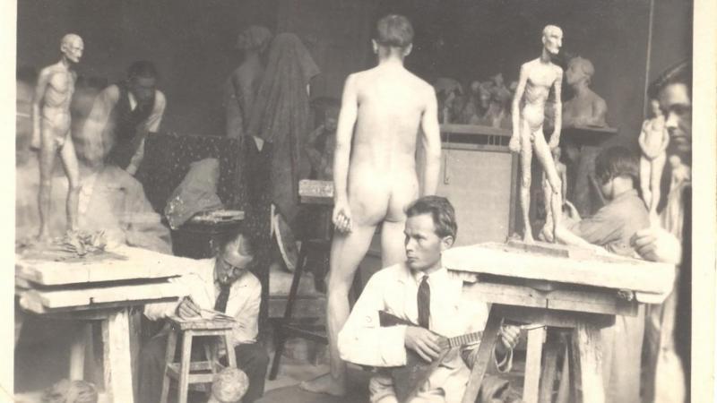 Kuvanveistoluokka, jossa on opiskelijoita veistämässä, sekä huoneen keskellä alaston miesmalli.
