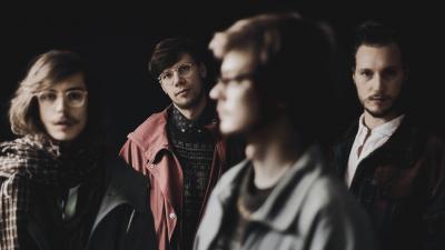 OK:KO yhtye seisoo hämärässä huoneessa. Kuvassa olevat hahmot ovat muuten epätarkkoja, paitsi Okko Saastamoisen kohdalta. Hän seisoo kuvassa taempana, joten kuvassa on syvä vaikutelma.