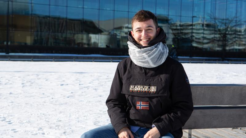 Exchange student Pablo Gill sits in front of the Music Centre in Helsinki.