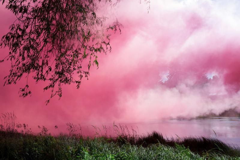 Vaaleanpunaista savua leijailee jokimaiseman päällä.
