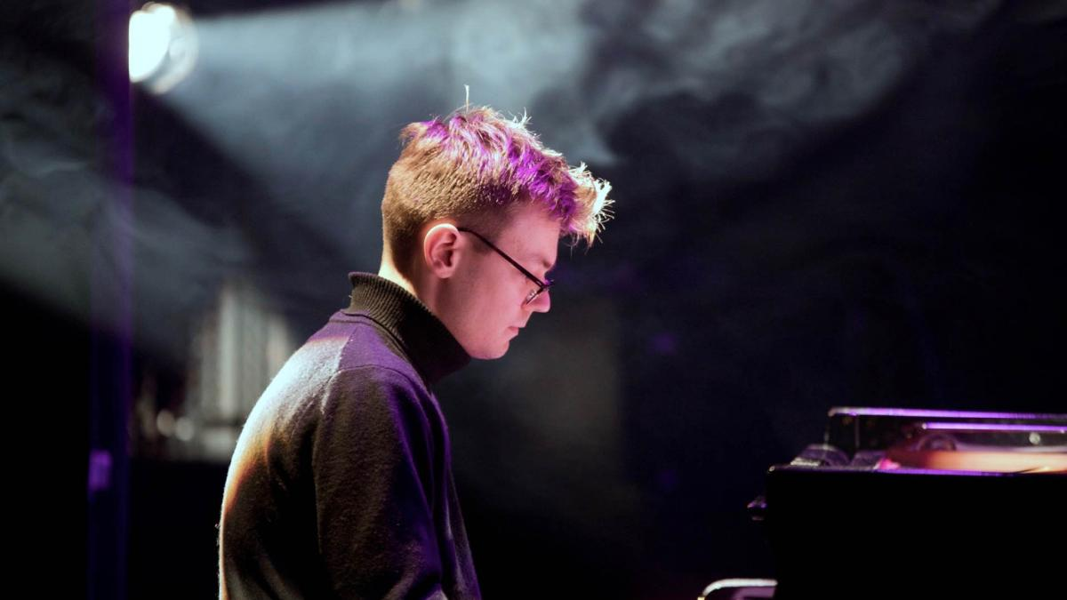 Toomas soittaa pianoa tunnelmallisessa kuvassa. Spottivalo on kohdistettu häneen ja ilmassa leijuu savua. Kuva on tumma.