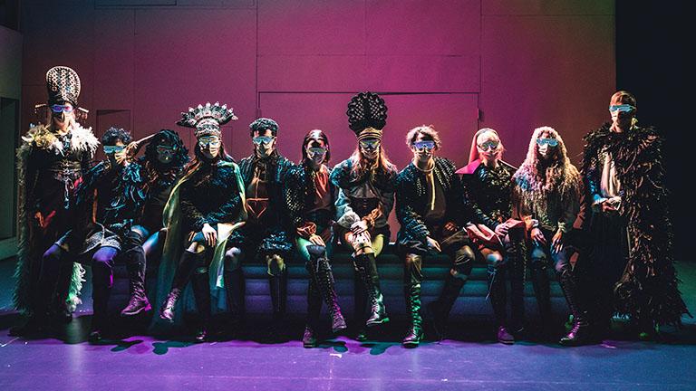Kuvassa 11 henkilöä istuu rivissä rooliasuissa.